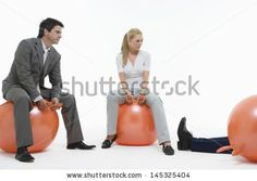 Young couple sitting on space hoppers and looking at fallen man against white background by bikeriderlondon, via ShutterStock