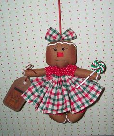 """Primitive Gingerbread Christmas Doll with Lollipop      This tiny cutie is handmade by me :) She measures about 6"""" tall,& she is made from brown cotton fabric.Her blouse and bloomer are red with white dots, her skirt; the colors of Christmas; red, green and white. She has a bow that matches her skirt. I hand stitched her nose with red DMC embroidery thread. She has embroidery thread hanger attached to the top of her head,for hanging on a tree, wreath or wall."""