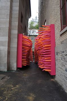Hundreds of pool noodles invade an abandoned alley in Québec City, Canada, for the Delirious Frites installation created by creative collective Les Astronautes.