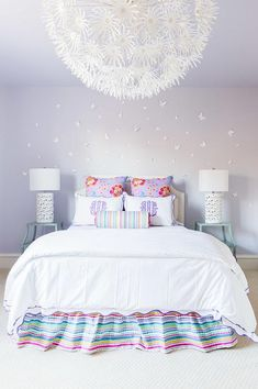 Laura Burleson Interiors - Purple girl's bedroom a purple wall clad in white decorative butterflies lined with a white bed dressed in purple monogrammed shams, purple floral pillows and a colorful ruffled bed skirt flanked by tiered turquoise nightstands illuminated by an Ikea PS Maskros Pendant Lamp.