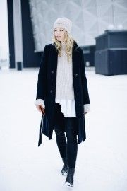 Anouk Yve looks ultra cute and cosy in this knitwear heavy outfit consisting of a matching cream sweater and beanie, black jeans, and a sleek navy Ganni overcoat. Coat: Ganni, Knit: Closed, Boots: Edited.de.