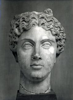 Marble idealised head from a statue of a woman wearing a crown with busts attached to it.