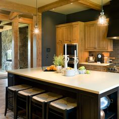 WOW! Keep the oak, do a dark charcoal on the walls (maybe even a chalkboard paint), that makes it look more modern, probably easier than painting the cabinets! Paint the Island and Barstools BLACK to go w our table!