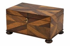 Parquetry box in geometric pattern of multi-woods on large bun feet. England, 1920.