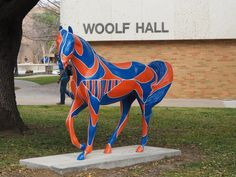 The mascot for the University of Texas at Arlington is the maverick. Periodically, students are given the equivalent of a blank canvas -- in this case a blank horse -- which is subsequently painted and placed around campus like this one near Woolf Hall. And yes, sports team colors are orange and blue.