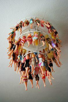 Carcasse d'abat-jour métallique sur laquelle sont suspendues une centaine de petites poupées bon marché. ~~ Doll-chandelier