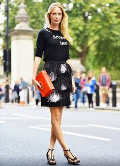 Poppy Delevingne in a sweater, feather skirt, and heels