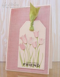 handmade greeting card ... mostly pink with pops of green ... light pink tag on darker pink background ,.. machine sewn edges .. stamped tulips with the flowers stamped a second time and the flower part cut out and popped up over the stamped one ... pleasing look ... luv this card!!