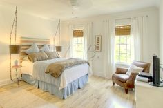 bleached hardwood floor, light cream walls, washed denim bed skirt, striped lamps, hanging side lamps with inverted drum shades, striped upholstered headboard, bamboo blinds, vintage leather chair, linen tab top curtains