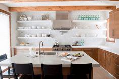 amenagement cuisine bois et blanc, avec des meubles hauts et bas en bois etageres et vaisselle blanche, aspirateur inox, poutres apparentes, ilot central