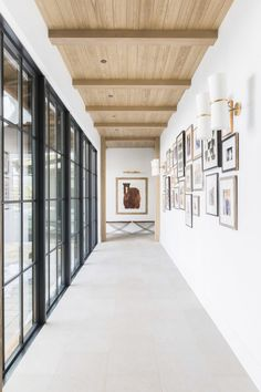 Mountain Chic Meets Modern Farmhouse in a Rustic Refined Retreat. Hallway with wood beamed ceiling and gallery wall of framed photos.