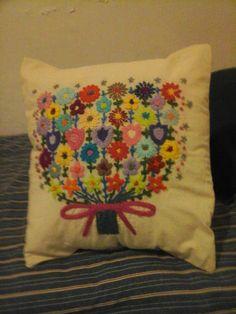 Flores bordadas sobre almohadón por R.S.