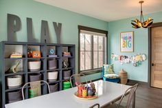 The big wooden letters just make this contemporary playroom features walls painted green fitted with a dark gray framed window next to side by side gray open shelving units filled with gray dip dyed woven bins. Homework room boasts a long, lacquered desk lined with Tolix Chairs.