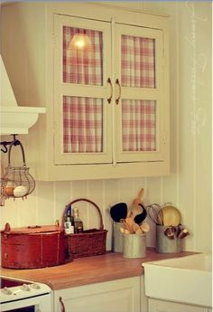 "Instead of fully remodeling, spice up kitchen cabinets by replacing door panel inserts with cute curtains. Use low profile barrel brackets and 3/8"" rod on backs of door frames."