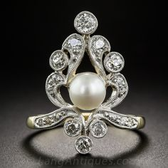 Edwardian Natural Pearl and Diamond Dinner Ring. Edwardian era grace and refinement are beautifully exemplified in this delightful dinner ring, dating from the first or second decade of the twentieth century. The artful one-way design is centered with a satiny white natural oriental pearl embellished by an array of bright white old mine-cut diamonds, all of which are accentuated in platinum over 18K yellow gold and finished with delicate milgraining.