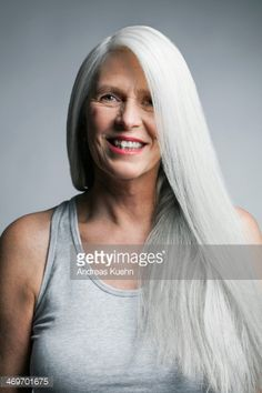 Mature woman with long, straight, silvery, grey hair in front of a grey background laughing.