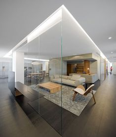 A large glass vitrine holds rooms like exhibits at the centre of this apartment in Singapore.