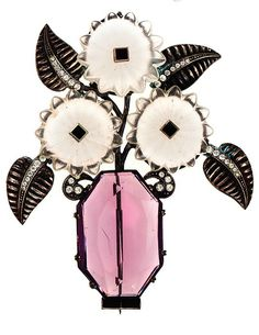 From The Collection of Elizabeth Taylor. AN ART DECO BROOCH, BY JDB, PROBABLY 1920S-1930S. Comprised of 835 silver; of embellished frosted glass, jet glass, a large simulated amethyst and rhinestones, designed as a vase with flowers, signed JDB. #JDB #ArtDeco #ElizabethTaylor #brooch