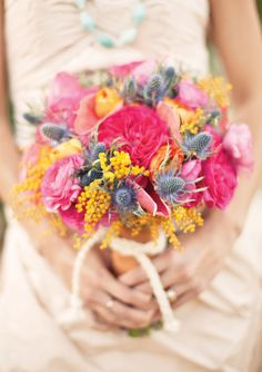 hot pink garden rose, yellow acacia, blue thistle, coral anthirium, and ranunculus bouquet by JL Designs, photographed by Gabriel Ryan Photographers