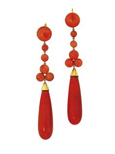 A pair of coral pendent earrings   Each elongated coral corallium rubrum drop to a cabochon coral trefoil and line surmount, 9.7cm long