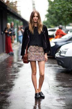 Black sweater, leather jacket, patterned skirt, boots or black flats. Black tights.