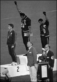 1968 Olympics. Peter Norman wearing the Olympic Project for Human Rights badge while Tommie Smith and John Carlos raise the Black Power salute.