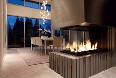 Steel and concrete fireplace reflecting light from dining room pendants
