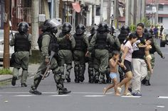 A family runs for shelter after tear gas was shot by riots police during a massive protest in Colon City, Panama