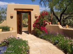 Courtyard path planters and planting ideas. A lot of elements and style make up the atmosphere of this courtyard. Wood, stone, plants, and earth tone color stucco work well together to create a southwest feel in this Tucson, Arizona home.