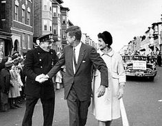 Senator John F. Kennedy & Jackie greeting Boston police officer on Chelsea Street in south Boston. ~ 1958.