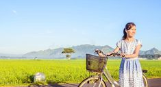 Photo about A little girl smile with a bicycle in the field. the mountain and clear sky in the behind. Image of mountain, blue, behind - 114519387