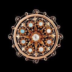BROSCH med gammalslipad diamant ca 0.20 ct samt 8 st vita cabochonslipade opaler.