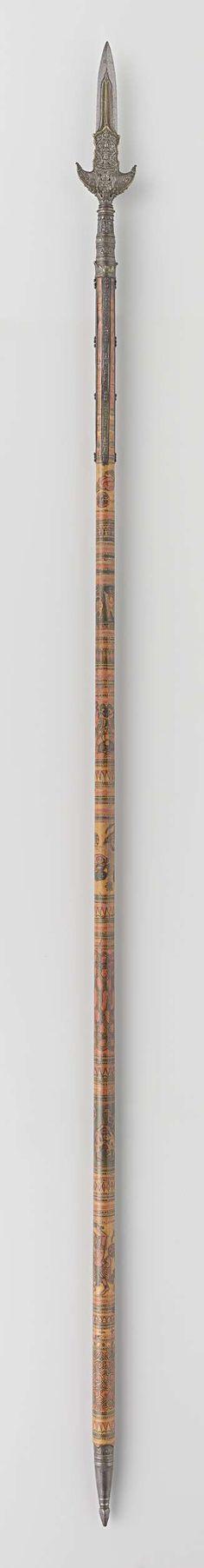   Partizaan van het wapenrek door Indische groten geschonken aan Gouverneur-Generaal J.C. baron Baud, c. 1700 - c. 1800   Ronde houten schacht beschilderd in zwart, rood, geel en groen met voorstellingen van Boddhisattva's, menselijke figuren en geometrische motieven. Onderzijde schacht heeft ijzeren kegelvorm met geschulpte rand en toelopend in stompe vierkante punt. Brede kling uitlopend in scherpe punt, met vier lippen. Kling is rijk versierd in reliëf met boddhisattva's en bloem- en…