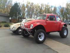 Baja bug on a bus frame next to a stock bug.