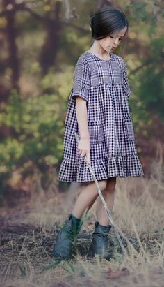 "Sweet pink and black check double sided cotton fabric with two large pockets to put fun treasures in and 3/4 length sleeves. Ruffled hem gives this dress a very fun and girly look. The model is 48"" ta"