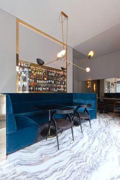 Glam #restaurant interior with blue velvet seating + #modern lighting