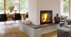 Die Fenster lassen viel Licht ins Haus und geben den Bewohnern das Gefühl, Teil der Natur zu sein. Ein Kamin teilt das Wohnzimmer in zwei offene Bereiche und sorgt im Winter für romantische Stunden. - Haus Schauer