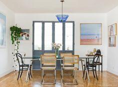 Sala de jantar com galeria de quadros e cadeira de modelos diferentes com a thonet e cesca.