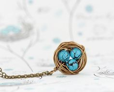 Turquoise Bird Nest Necklace  This whimsical, rustic little brass bird nest necklace is made from wrapped antique brass colored wire. Nestled inside are three robin's eggs made from crackled turquoise colored beads.  Perfect idea for a Mother's Day gift.