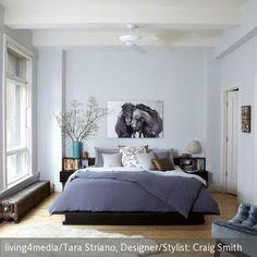 Hellblaue Wandfarbe, violettblaue Bettwäsche und ein gemütlicher Polstersessel mit taubenblauem Samtbezug bilden einen modernen Kontrast  zum klassischen  …