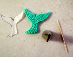 a great tutorial on how to make a fondant mermaid tail...without a cookie cutter (to use as a cupcake topper).