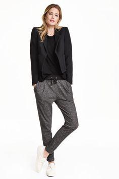 Pantaloni de jogging: Pantaloni de jogging din molton melanj, cu elastic şi cu şnur în talie, cu buzunare laterale. Model conic pe picioare, cu pliuri în faţă.