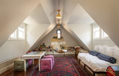 """Before the remodel a third-story attic was a utilitarian storage space. With the addition of large dormer windows on either side of the room, there's now enough headroom for it to be a play area. """"After we carefully thought through the storage bins and the addition of the platform bed, I thought the room needed a hanging element,"""" says Nelson of the now-beloved hanging chair."""