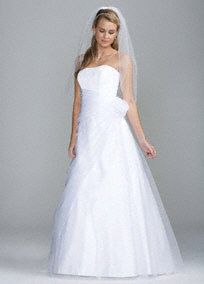 You will look stunning and chic as you walk down the aisle in this exquisite wedding gown! Beautifully fitted corset top is flattering & slimming. Satin A-line skirt features an organza side-drape overlay with a 3D flower detail at waist. The organza overlay drapes across back of skirt and meets at flower with a hook-and-eye closure. This unique design features a sweep train. Available in limited stores and online in White. Fully lined. Back zip. Imported polyester. Dry clean. A train that…