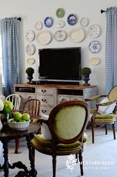 love the hanging plates on wall over the tv/cabinet - great mix of old and new