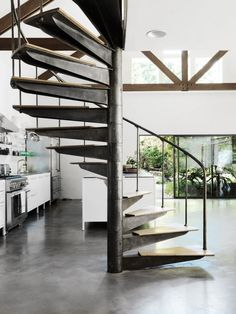 The kitchen is in a new extension of the house that leads to an outdoor patio. The steel spiral stair, polished concrete floor, and barn-style joists stand out against bright white walls.