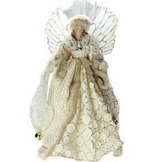 Angel is dressed in a lavish gingham printed cream and gold coat. The cuffs and front of coat are trimmed with fur  She has a gorgeous geometric printed cream and gold dress  Features stiffened white wings trimmed in gold and outlined in fiber optics  Under her dress there is a plastic cylinder...