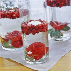 Place a silk rosebud in the bottom of a vase (place small weights inside the bloom) and then slowly fill the vessel halfway with water. Gently place a handful of cranberries on top of the water and then add a floating votive to the center.