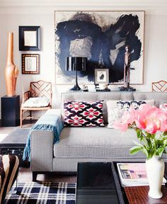 Gray couch in living room with modern art.