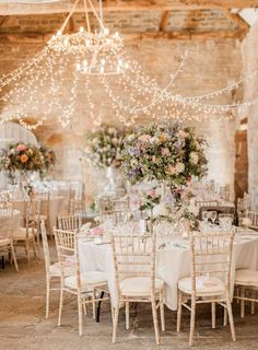 Romantic barn wedding decor featuring a pink colour scheme, peony & rose floral display as well as a hanging fairy light canopy.